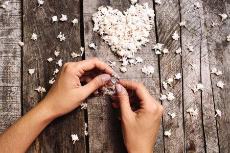 bague de mariage en mains et coeur blanc du fond de fleurs