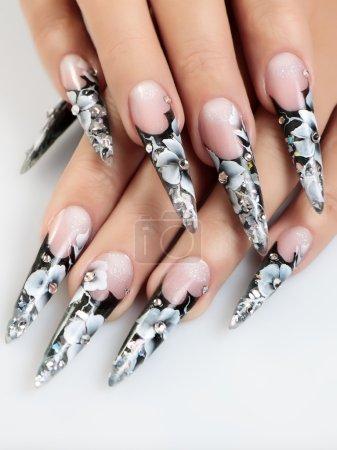 Photo pour Female hands with floral pattern on  nails. - image libre de droit