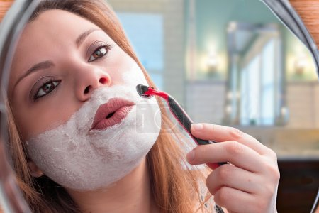 Photo pour Fille dans le miroir rasage avec rasoir - image libre de droit