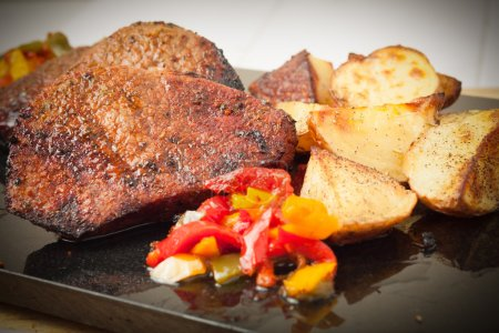 Succulent thick juicy portions of grilled fillet steak served with roasted potatoes and peppers on black granite board