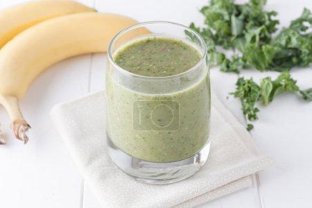 Photo pour Smoothie vert sur fond blanc, les ingrédients incluent des bananes, du chou frisé frais et des amandes - image libre de droit