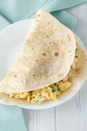 Photo for Breakfast egg burrito with cheese,  herbs and spices on white plate - Royalty Free Image