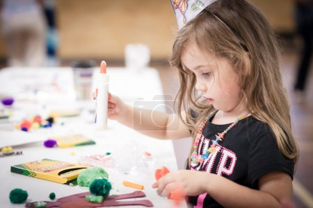 Photo for Little girl making handcraft at a table at a kids party - Royalty Free Image