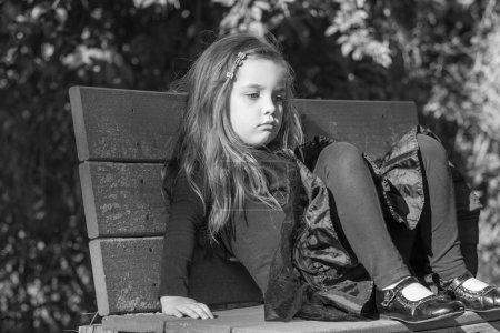 tired or bored little girl sitting on a bench, black and white image