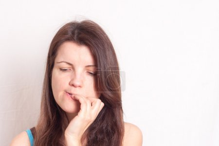 a portrait of a young woman biting her nails