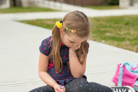 very sad caucasian little girl sitting on a sidewalk in front of school and worrying or crying