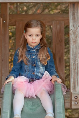 Photo for Little girl with two pony tails wearing a denim jacket sitting on top of a slide - Royalty Free Image