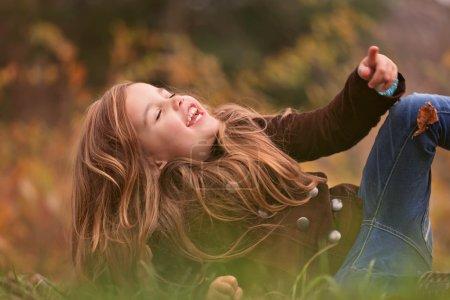 Foto de Una niña con cabello largo riendo y rodando sobre la hierba en un cálido día de otoño - Imagen libre de derechos