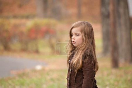Photo pour Une petite fille avec longtemps l'air très triste et regardant loin, disant au revoir à quelqu'un ou attendant quelqu'un - image libre de droit