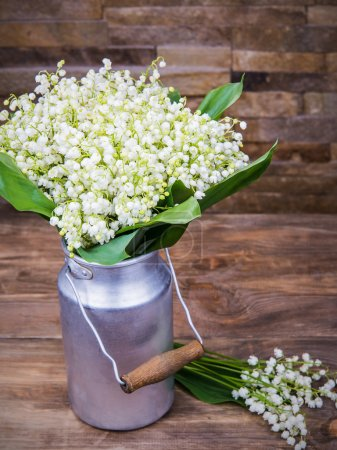 Bouquet of white lilies of the valley in aluminum containers on a wooden background