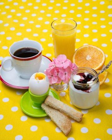 Photo pour Petit déjeuner avec café, pain grillé, œufs, jus d'orange, muesli, yaourt, fruits - image libre de droit