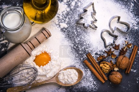 Photo pour Ingrédients pour les biscuits de Noël. Farine, plongeur, corolle, cuillère en bois, huile, lait, oeufs, noix de Grenoble sur tableau noir - image libre de droit