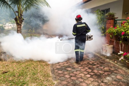 Worker fogging residential area with insecticides to kill aedes mosquitoes