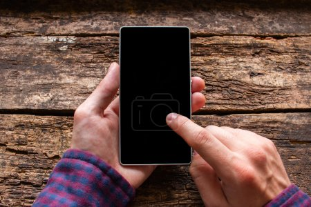 man touches the screen in the phone on a wooden background mockup