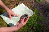 woman traveler checks with the route using a map and compass