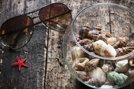 Sunglasses, seashells in a vase, starfish on a wooden background selective focus
