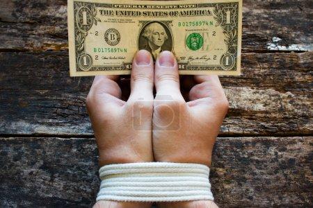 Photo pour Mains liées hommes et argent dans les mains - un symbole de l'esclavage - image libre de droit