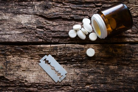 Handful of pills and blade for suicide on a wooden background