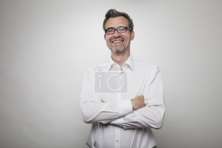 Smiling middle aged manager with crossed arms in white shirt