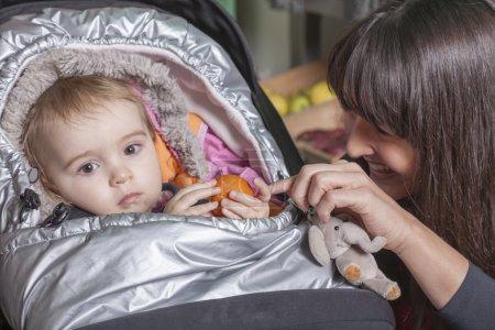 tired toddler girl in stroller with kidding sales girl in fruit