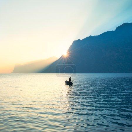 Photo pour Pêche de pêcheur au milieu du lac sous le coucher du soleil étonnant - image libre de droit
