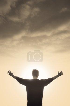 Photo pour Homme éclairés avec foi exultant sous la lumière de Dieu - image libre de droit