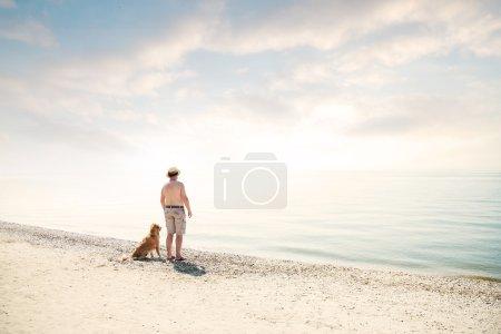 Photo pour Homme et crabot regardant la mer au coucher du soleil - image libre de droit