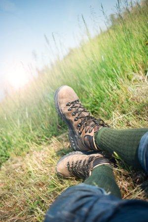 Photo pour Homme couché reposant dans l'herbe avec des bottes de trekking - image libre de droit
