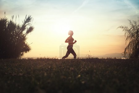 Woman running in the nature at sunset