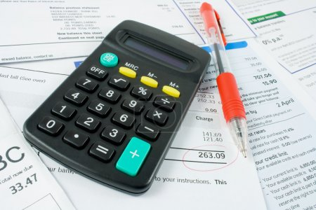 Calculator and pen on bank statements