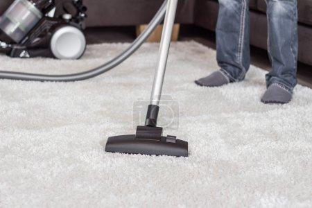 Un homme nettoie le tapis avec un aspirateur .