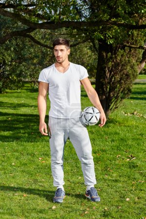 Young beautiful muscular man, soccer player holding the ball in hands on green grass in a clear day. Looking into the distance.