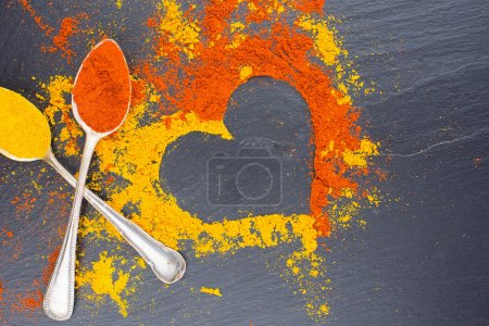 Colorful heart from spices on black background with two vintage spoons. Suggesting Valentines day concept.