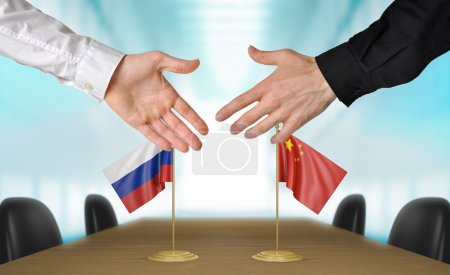 Photo pour Two diplomats from Russia and China extending their hands for a handshake on an agreement between the countries. - image libre de droit