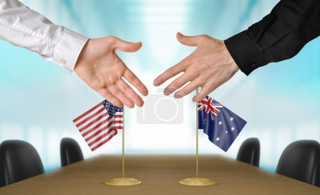 Photo pour Two diplomats from United States and Australia  extending their hands for a handshake on an agreement between the countries. - image libre de droit