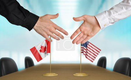 Photo pour Two diplomats from Canada and United States extending their hands for a handshake on an agreement between the countries. - image libre de droit