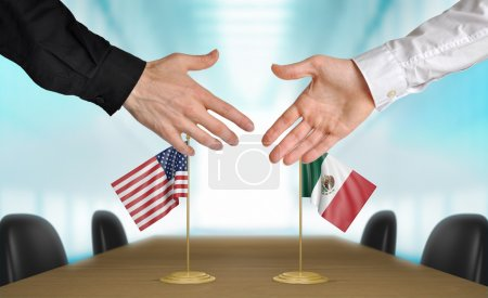 Photo pour Two diplomats from the United States and Mexico extending their hands for a handshake on an agreement between the countries. - image libre de droit