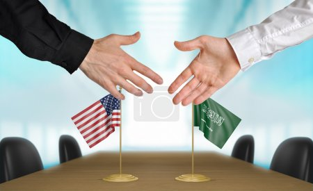 Photo pour Two diplomats from the United States and Saudi Arabia extending their hands for a handshake on an agreement between the countries. - image libre de droit