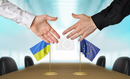 Photo pour Two diplomats from Ukraine and European Union extending their hands for a handshake on an agreement between the countries. - image libre de droit