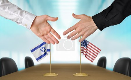 Photo pour Two diplomats from Israel and United States extending their hands for a handshake on an agreement between the countries. - image libre de droit