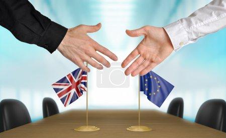 Photo pour Deux diplomates du Royaume-Uni et Union européenne étendant leurs mains pour une poignée de main sur un accord. - image libre de droit