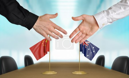 Photo pour Two diplomats from China and Australia extending their hands for a handshake on an agreement between the countries. - image libre de droit