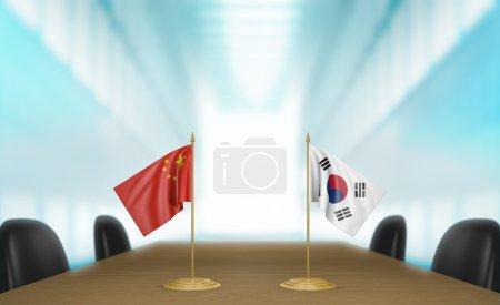Photo pour Drapeaux de table miniature pour la Chine et la Corée du Sud à une table de réunion pour les négociations et discussions diplomatiques. - image libre de droit
