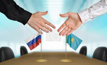 Photo pour Two diplomats from Russia and Kazakhstan extending their hands for a handshake on an agreement between the countries. - image libre de droit