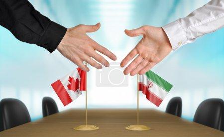 Photo pour Deux diplomates du Canada et l'Iran s'étendant la main pour une poignée de main sur un accord entre les pays. - image libre de droit