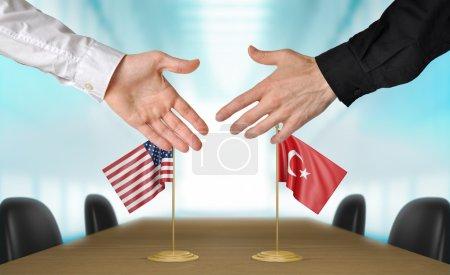 Photo pour Deux diplomates depuis les Etats-Unis et la Turquie s'étendant la main pour une poignée de main sur un accord entre les pays. - image libre de droit