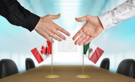 Photo pour Deux diplomates canadiens et mexicains s'étendant la main pour une poignée de main sur un accord entre les pays. - image libre de droit