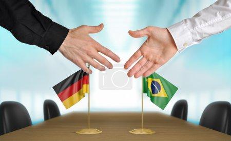 Photo pour Deux diplomates d'Allemagne et du Brésil qui s'étend de leurs mains pour une poignée de main sur un accord entre les pays. - image libre de droit