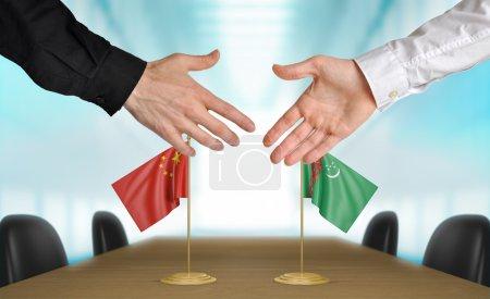 Photo pour Deux diplomates de Chine et le Turkménistan s'étendant la main pour une poignée de main sur un accord entre les pays. - image libre de droit