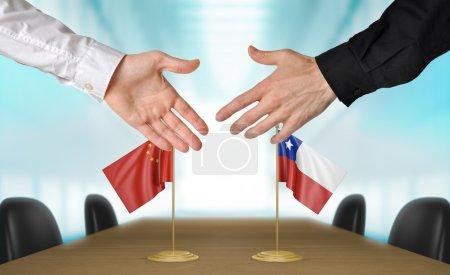 Photo pour Deux diplomates de Chine et le Chili s'étendant la main pour une poignée de main sur un accord entre les pays. - image libre de droit